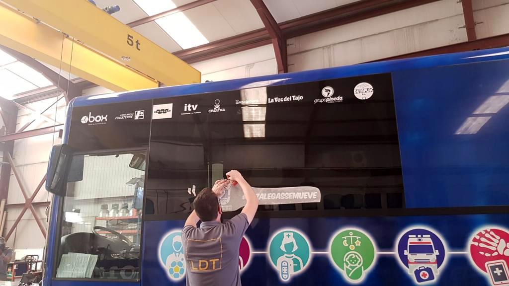 Trabajador preparando autobús para vinilar